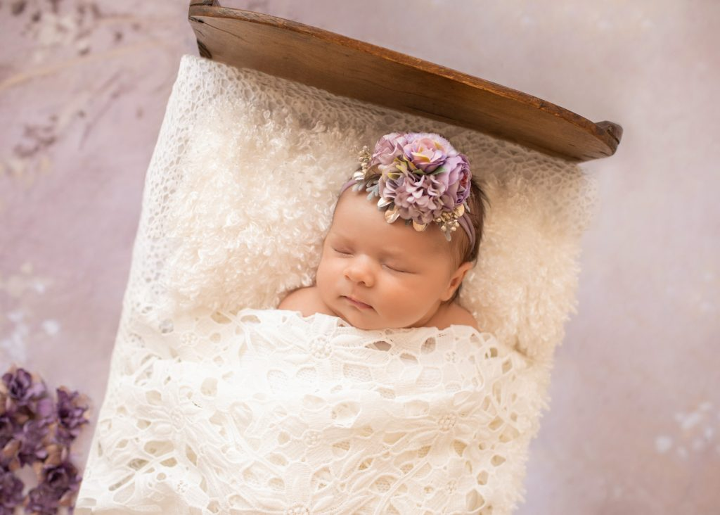 Close up tiny baby girl Bryce sleeps under white lace blanket in baby bed with purple flowers and matching headband