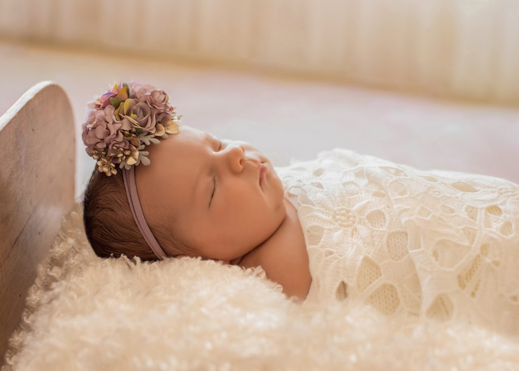 Profile tiny baby girl Bryce sleeps under white lace blanket in baby bed with purple flowers and matching headband