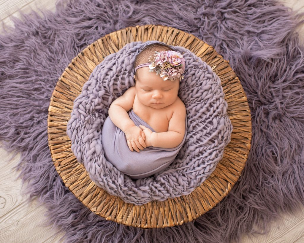 Newborn girl Bryce holds her hands with purple wrap and fur in brown basket