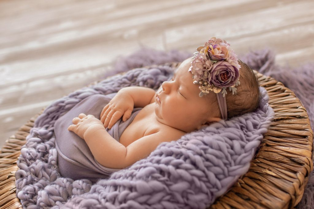 Profil newborn girl Bryce poses with purple wrap and fur in brown basket
