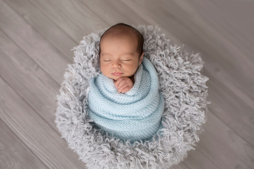 baby in grey stuffed bowl wrapped in pale blue knit blanket against grey wood floor
