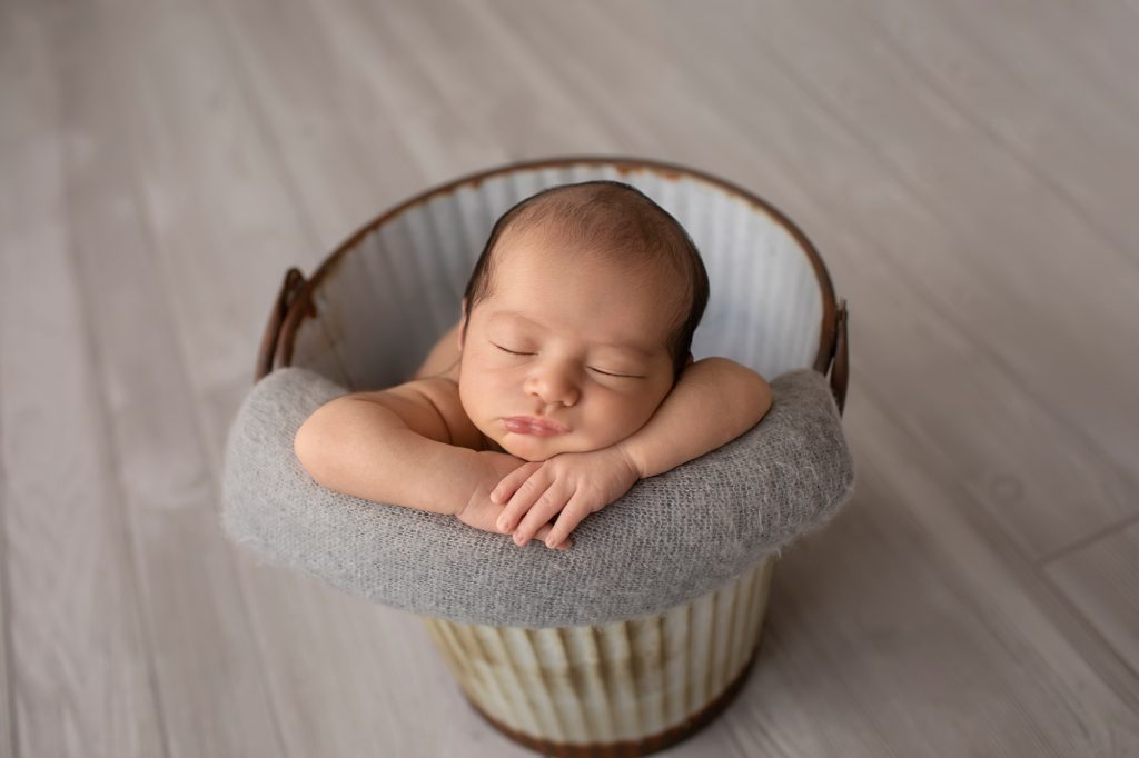 newborn image naked in metal bucket against grey wood floor