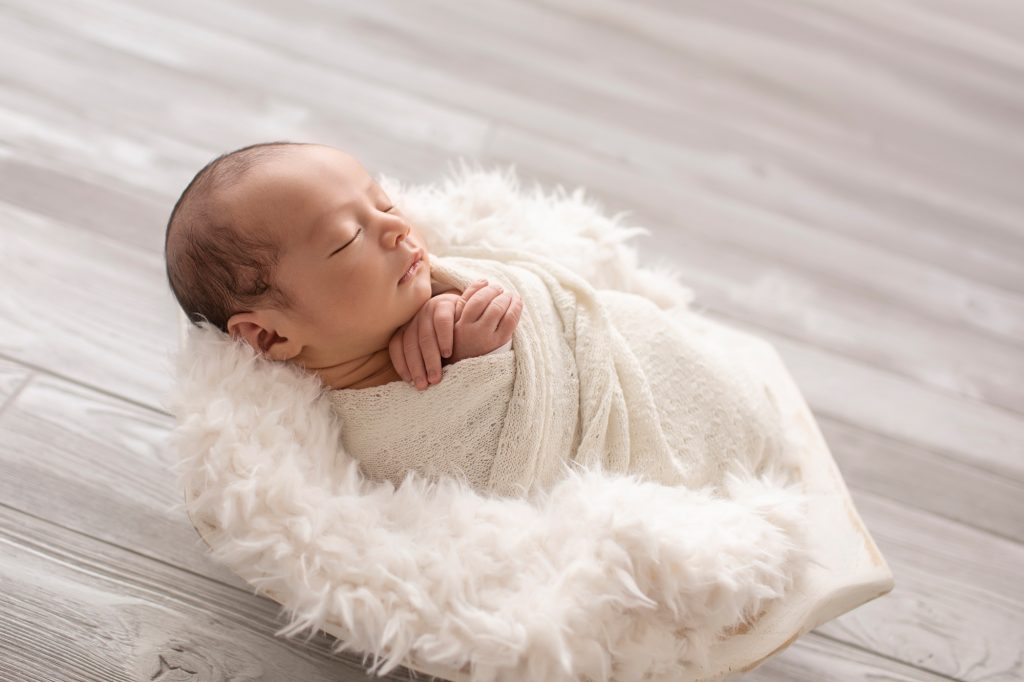 baby wrapped in white against back light in white fur stuffed bowl against grey floor