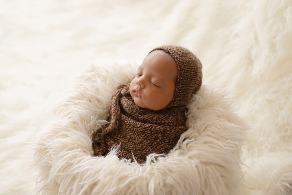 Lucas baby newborn wrapped like a brown potato sack with matching knit bonnet against back light