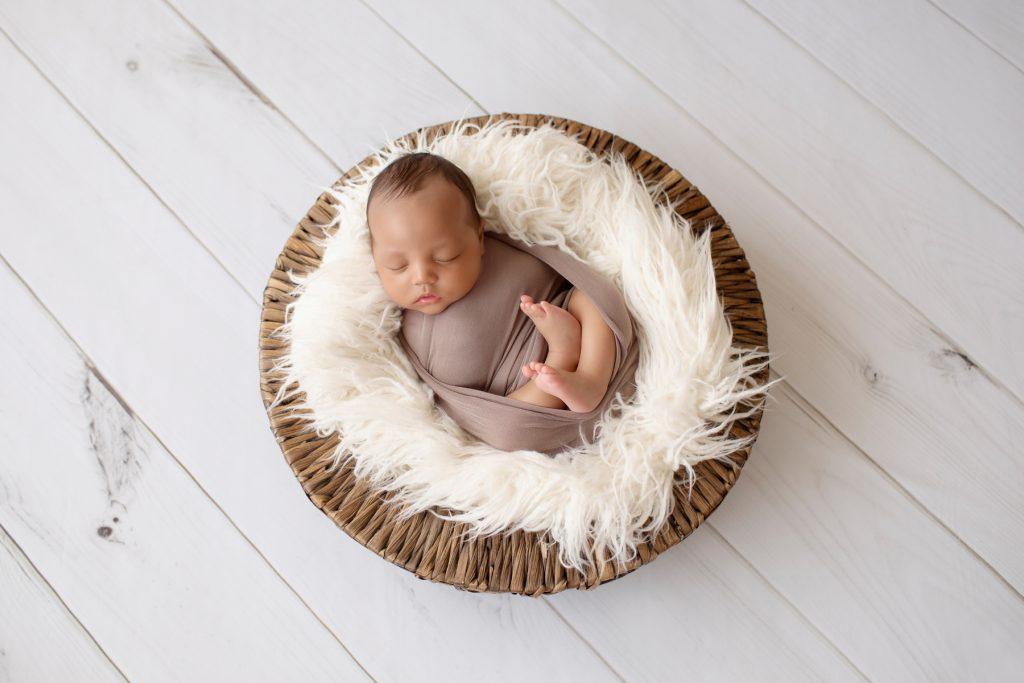 Lucas wrapped in brown swaddle in white fur stuffed wicker basket on white wood floor