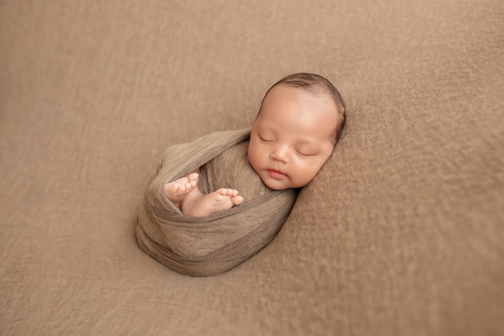 Smiling Lucas in brown swaddle with toes poking out and beautiful baby face toward camera