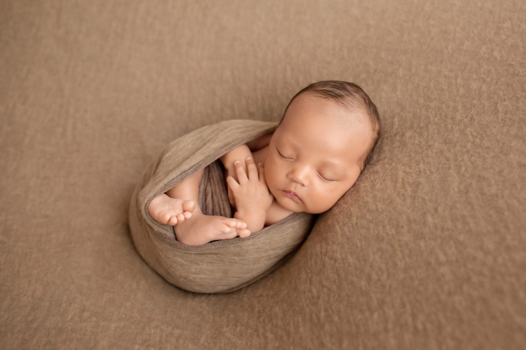 Lucas in brown swaddle with hands and toes poking out and beautiful baby face toward camera