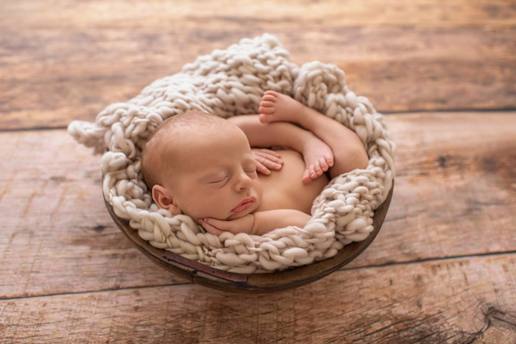 naked newborn baby on beige chunky knit blanket in rustic brown bowl against brown wood floor and backlight