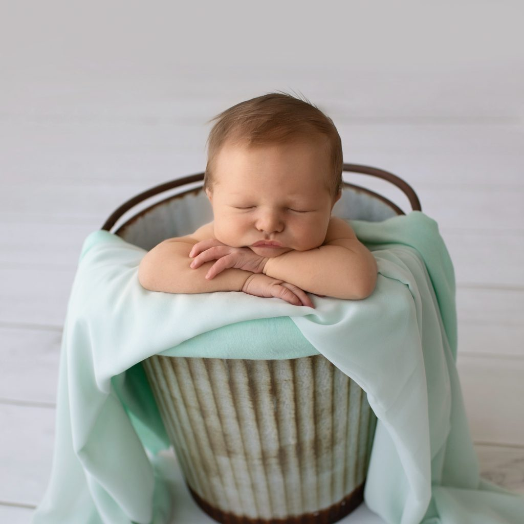 Newborn photography baby boy poses in metal bucket with mint green blanket on grey floor