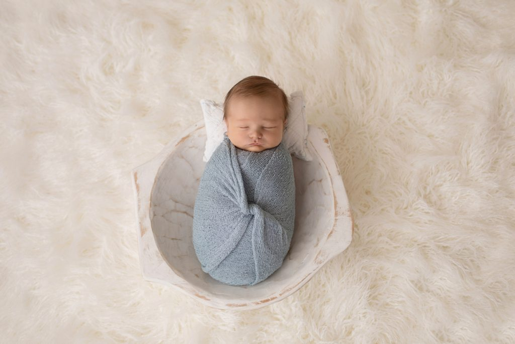 Newborn photography baby boy swaddled in pale blue posed in white wooden bowl on white fur