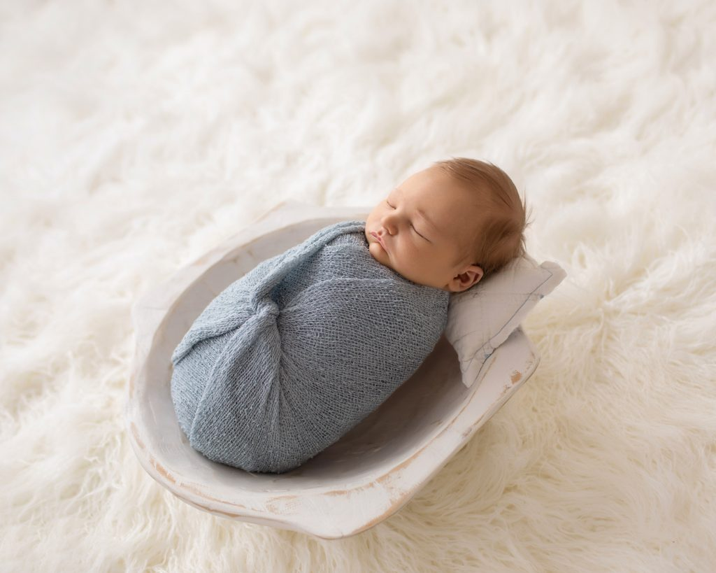 Newborn photography baby boy swaddled in pale blue posed in white wooden bowl on white fur with backlight