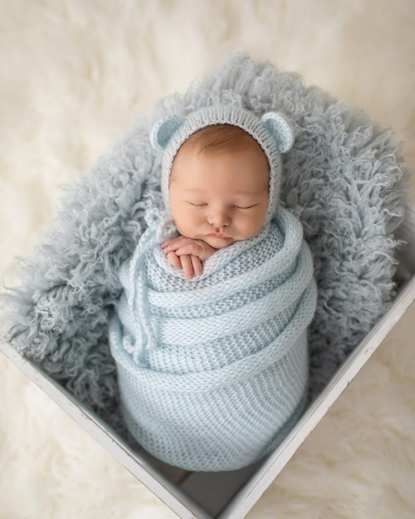 Newborn Gabe swaddled in a pale blue knit potato sack with matching bear bonnet in a fur stuffed white crate