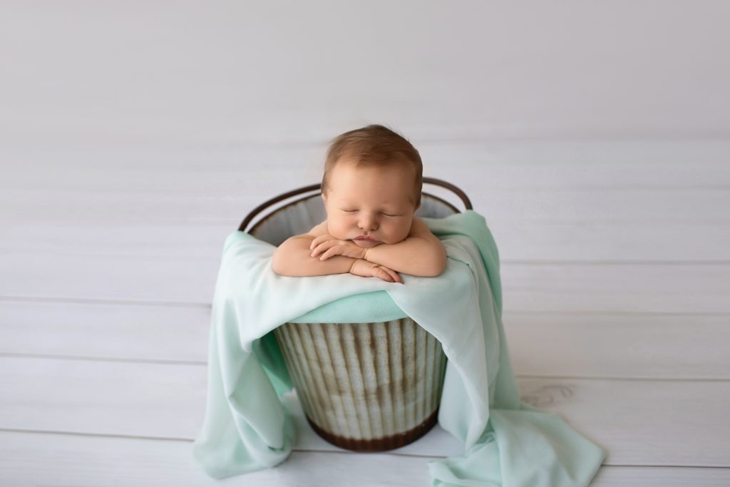 Newborn photography baby boy poses in metal bucket with mint green blanket on grey floor Gainesville FL