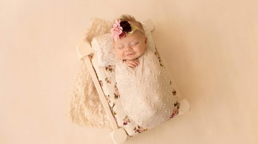 mini newborn photo session girl in ivory lace on floral bed floral headtie Gainesville FL