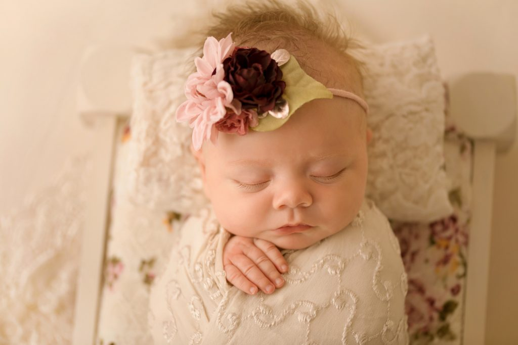 mini newborn photo session girl in ivory lace on floral bed floral headtie