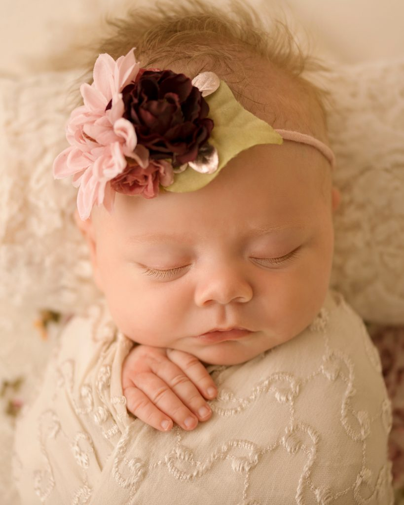 mini newborn photo session girl close up gorgeous eyelashes tiny baby fingers ivory lace on floral bed floral headtie Gainesville FL