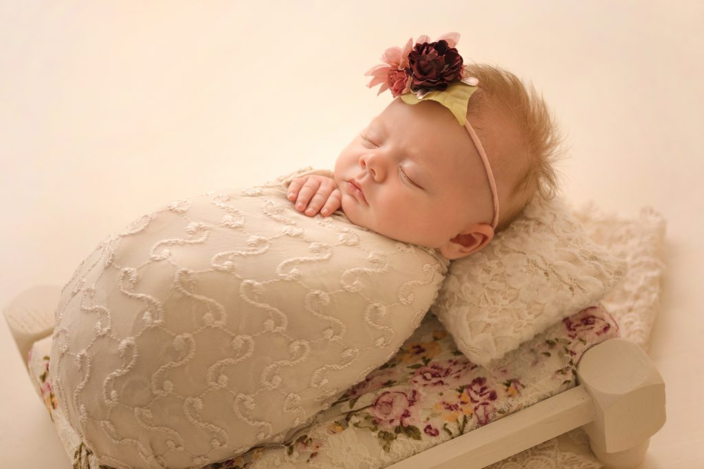 mini newborn photo session girl ivory lace on floral bed floral headtie
