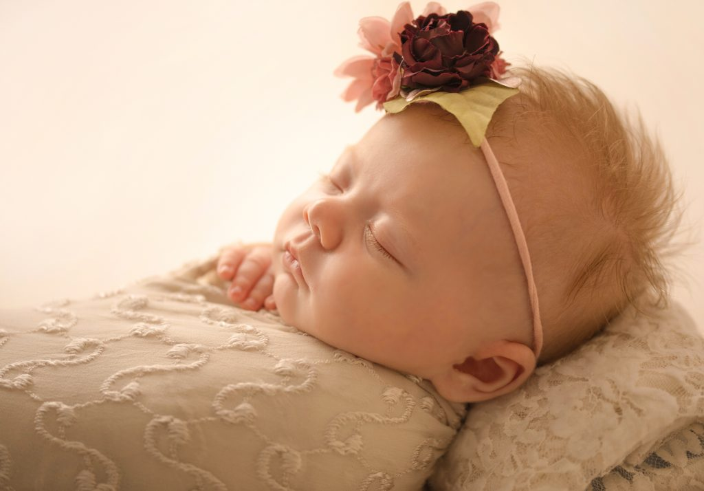 mini newborn photo session girl close up backlit gorgeous eyelashes tiny baby fingers ivory lace on floral bed floral headtie Gainesville FL