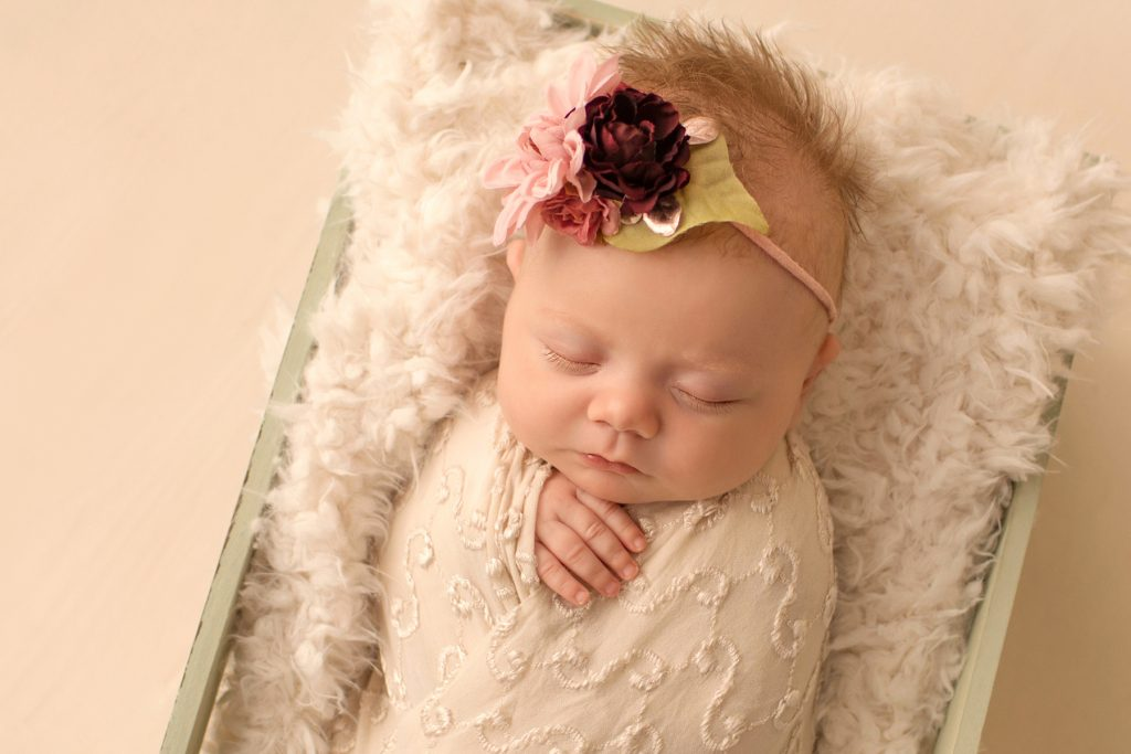 newborn photo session girl close up beautiful baby face gorgeous eye lashes ivory lace in sea green wooden crate floral headtie Gainesville FL