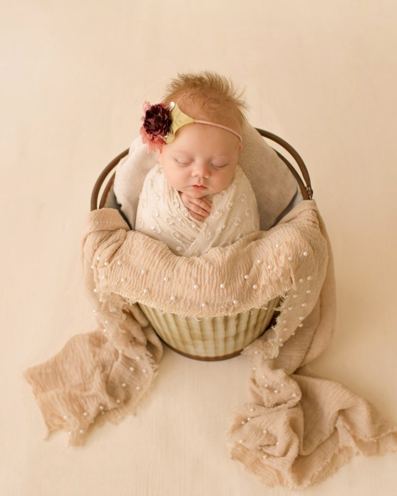 newborn girl baby in a bucket ivory lace in floral headtie Gainesville FL