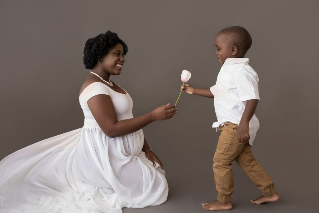 boy hands pink rose for newborn sister to pregnant mom white chiffon toss maternity gown