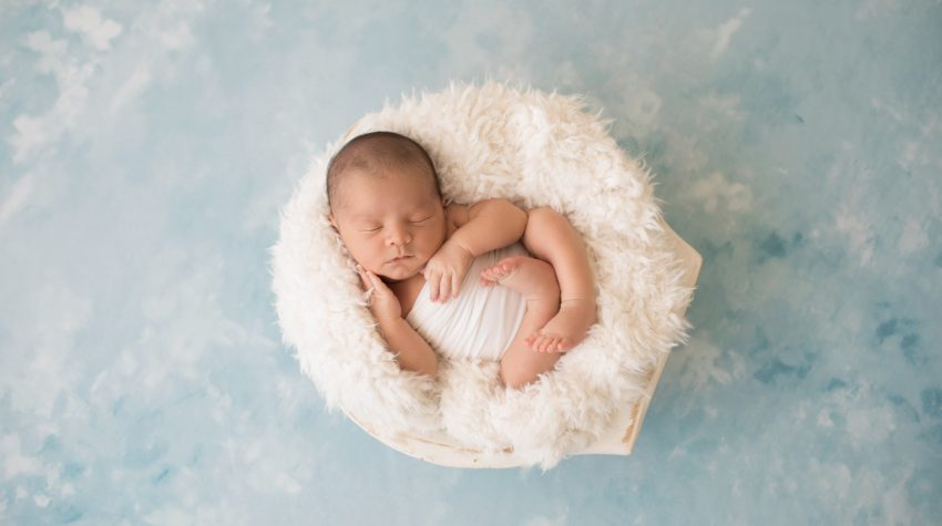Newborn photography baby boy in white swaddle cupping his baby cheek with his tiny newborn hands sleeps in white fur stuffed wooden bowl on pale blue clouds Gainesville FL newborn mini photo session