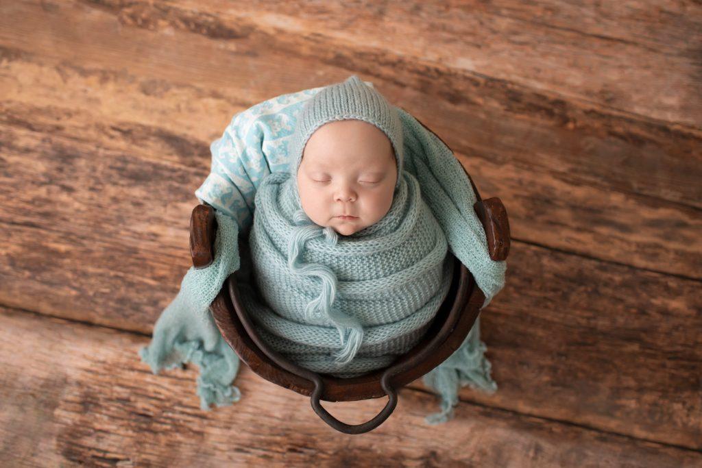 baby boy in wood bucket blue knit potato sack matching bonnet Gainesville FL newborn photos