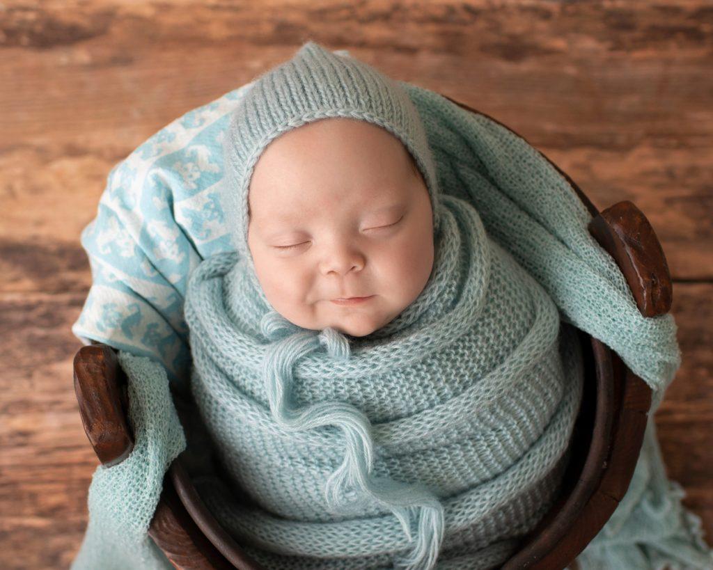 baby boy in wood bucket big smile blue knit potato sack matching bonnet Gainesville FL newborn photos