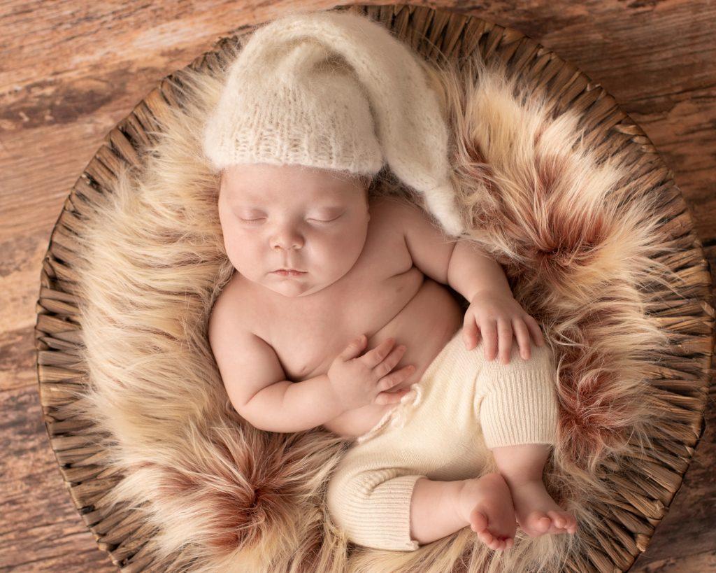 baby boy in fur basket on wood floor cream sleepy hat and pants Gainesville FL newborn photos